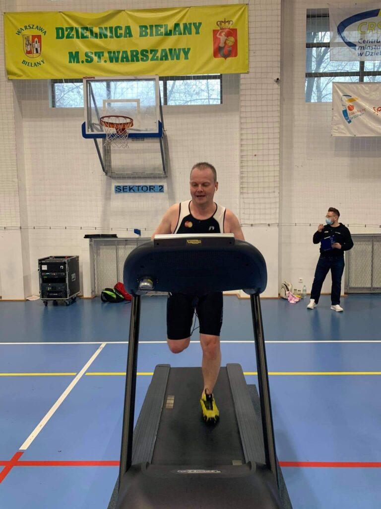 Na pierwszym planie Burmistrz Dzielnicy biorący udział w triathlonie, biegnący na bieżni. W tle hala sportowa i okna wychodzące na zewnątrz.