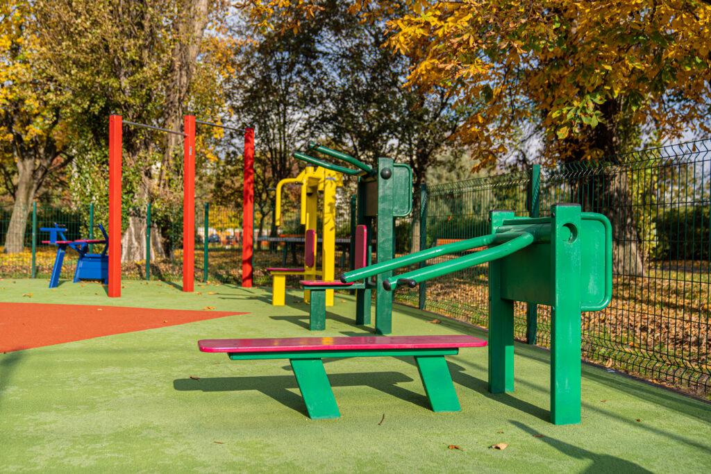 Niezwykle barwne jesienne zdjęcie siłowni plenerowej przy zewnętrznym obiekcie sportowym Syrenka. Znajdują się na niej barwne urządzenia do ćwiczeń w kolorach żółtych, zielonych, niebieskich i czerwonych postawione są one na miękkim zielono-ceglaste podłoże tartanowe.  Widać kawałek boulderu do wspinania.