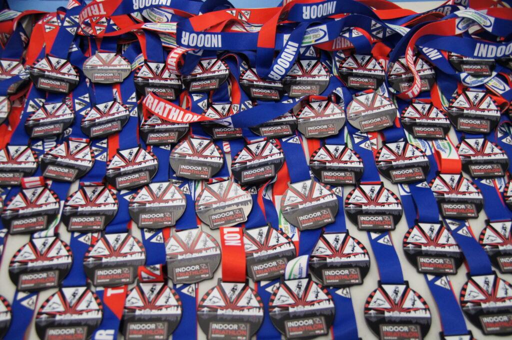 bardzo duża ilość medali w kolorystyce czarno-czerwono-białej na niebieskim obrusie dla zawodników triathlonu