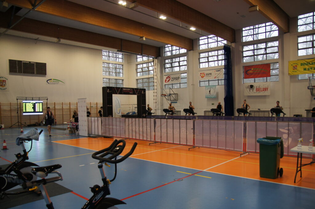 zawodnicy na rowerach stacjonarnych, w tle hala sportowa wraz z banerami