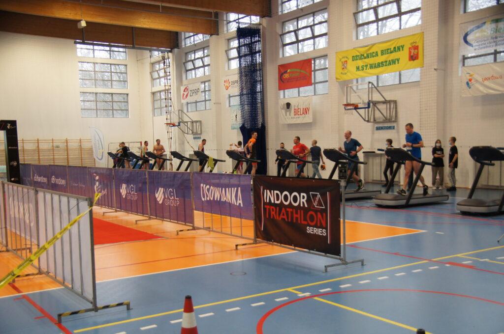 Duża ilość mężczyzn na bieżniach na tle hali sportowej, po środku sali wyznaczony tor dla przechodzących wraz z logami sponsowrów