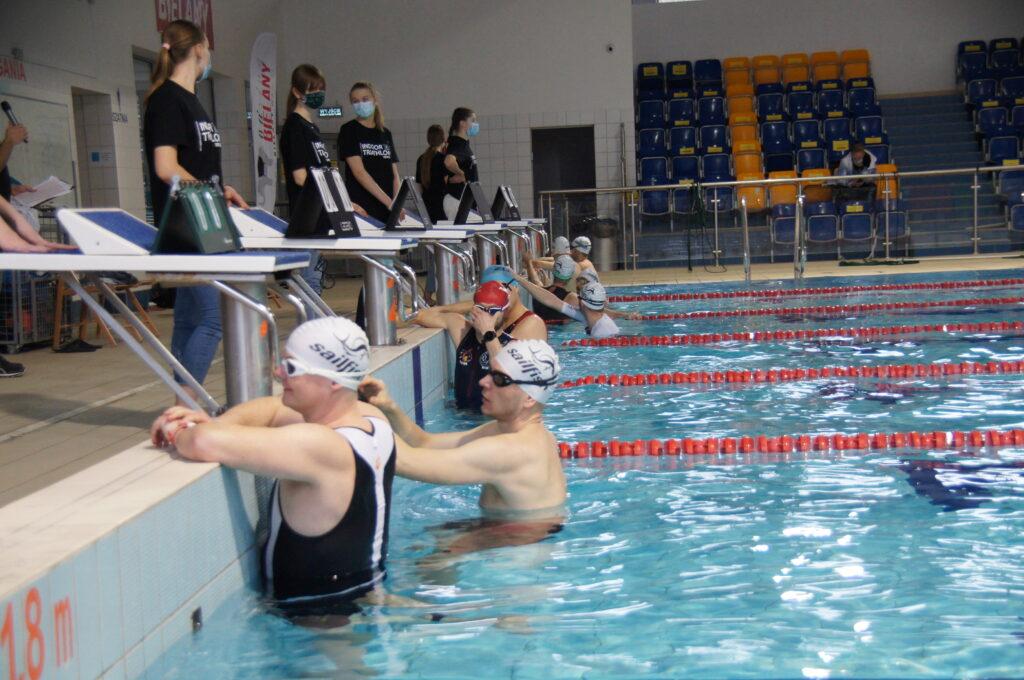 pływający zawodnicy przygotowujący się do startu w zawodach, na pierwszym planie Burmistrz Dzielnicy w tle pływalnia CRS Lindego