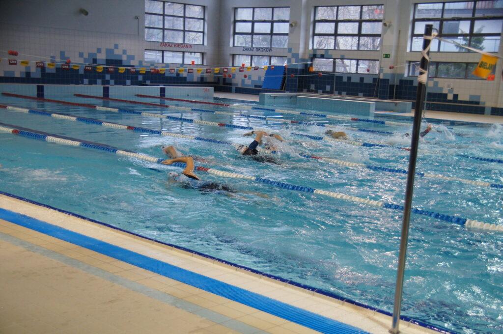 pływający zawodnicy na pływalni CRS Bielany, za zdjęciu nie widać dokładnych postaci, za to widać plusk wody