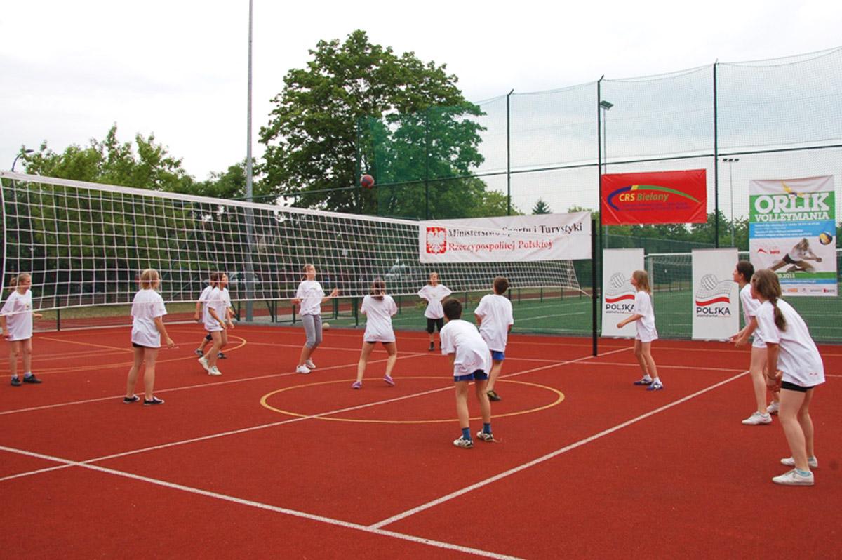 Kilku młodych chłopców grających w piłkę nożną na zielonej murawie ogrodzonego, zewnętrznego obiektu sportowego. W tle budynek gospodarczy.