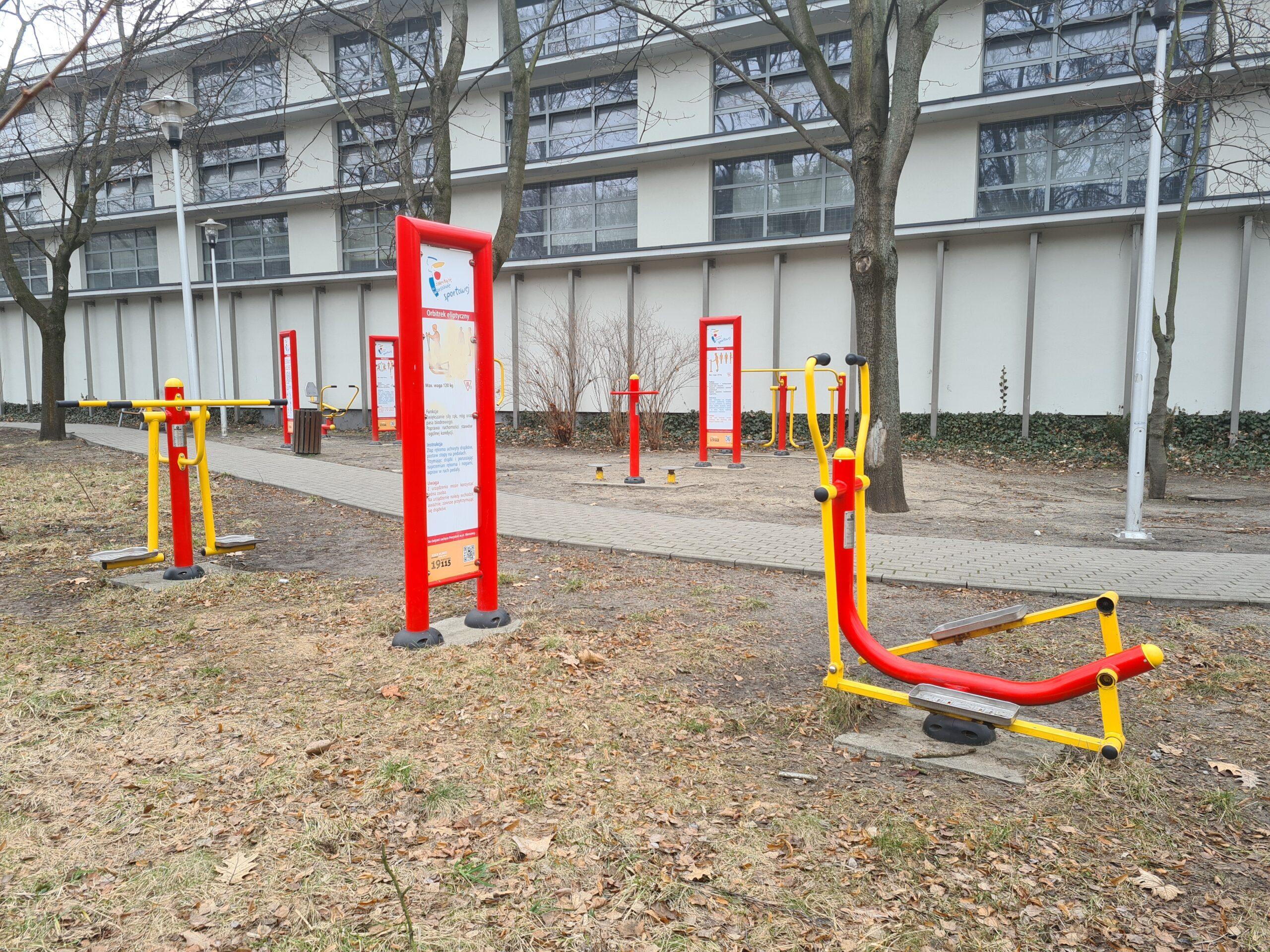 2 różniące się zdjęcia siłowni plenerowej Lindego: Zdjęcie siłowni plenerowej przy obiekcie sportowym Lindego. Znajdują się na niej urządzenia do ćwiczeń w kolorach żółtych i czerwonych postawione są one wokół drzew. W tle budynek CRS Bielany.