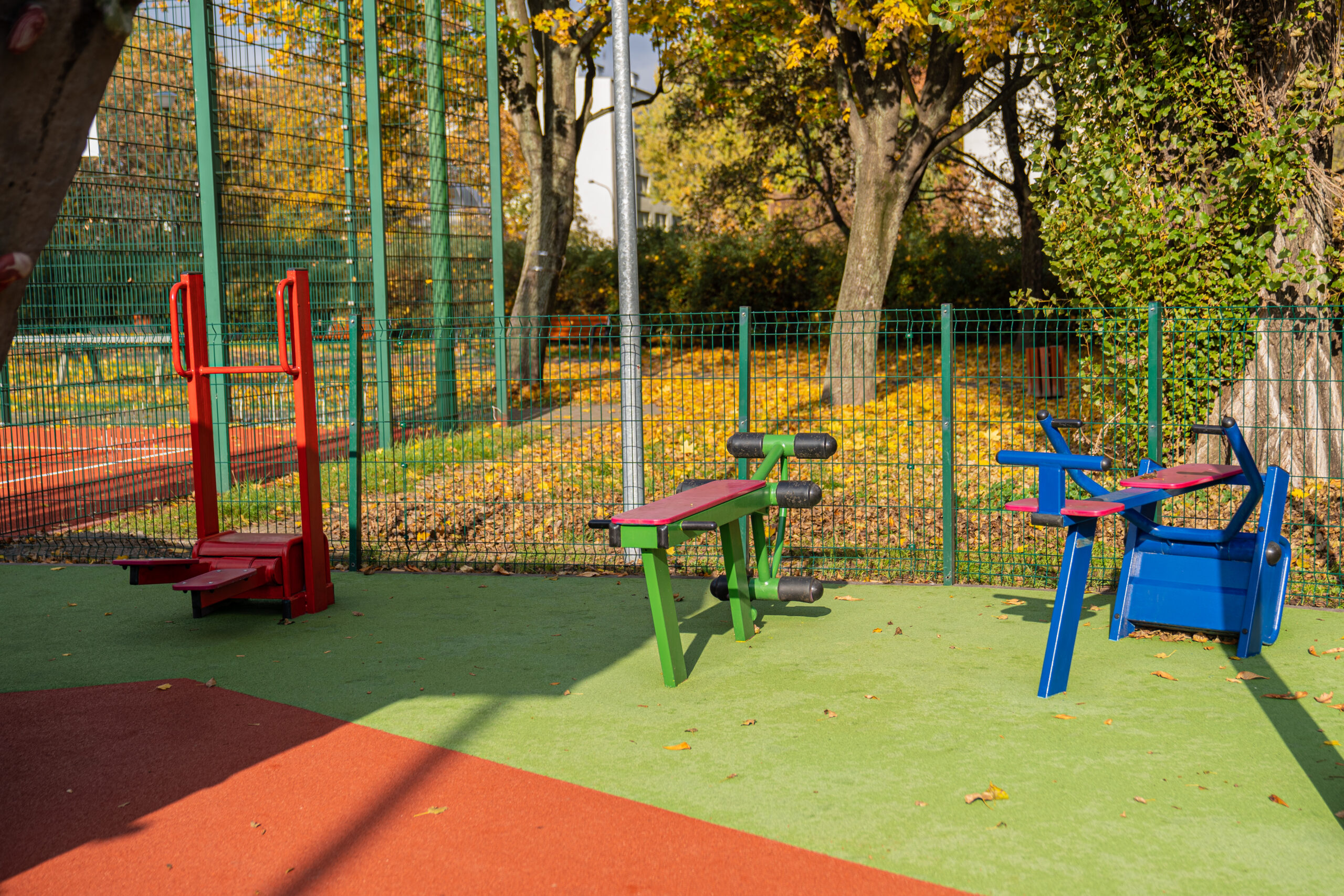 Niezwykle barwne jesienne zdjęcie siłowni plenerowej przy zewnętrznym obiekcie sportowym Syrenka. Znajdują się na niej barwne urządzenia do ćwiczeń w kolorach żółtych, zielonych, niebieskich i czerwonych postawione są one na miękkim zielono-ceglaste podłoże tartanowe.