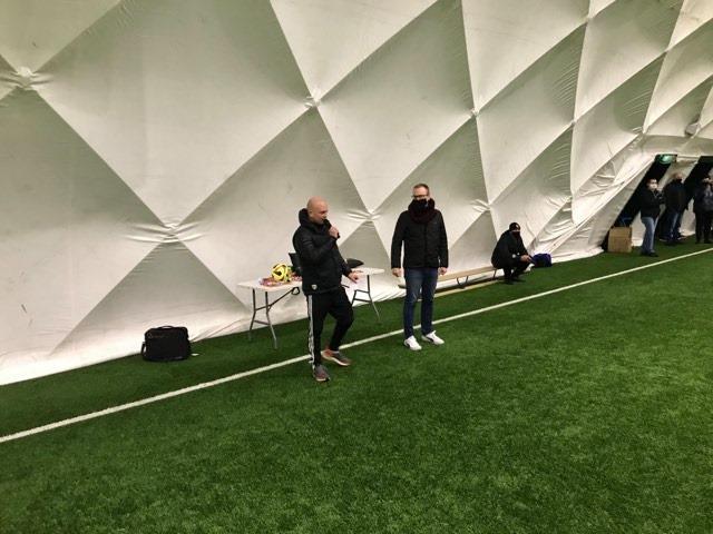 Dwóch dorosłych mężczyzn na otwarciu zawodów piłki nożnej. Jednym z nich jest Grzegorz Pietruczuk Burmistrz Dzielnicy Bielany. W tle biała ściana hali pneumatycznej oraz zielona murawa.