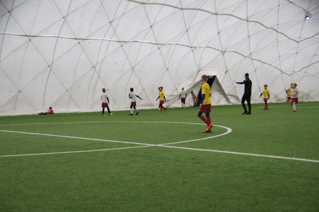 Kilkoro dzieci grających w piłkę nożną pod zadaszoną halą pneumatyczną w kolorze białym na zielonej murawie.