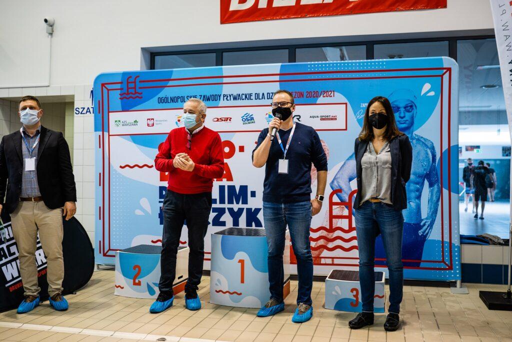 Cztery osoby dorosłe na tle dużego banera w przewagą koloru błękitnego przemawiają podczas rozpoczęcia zawodów. Stoją w maseczkach. Jedną z tych osób jest Grzegorz Pietruczuk Burmistrz Dzielnicy Bielany.