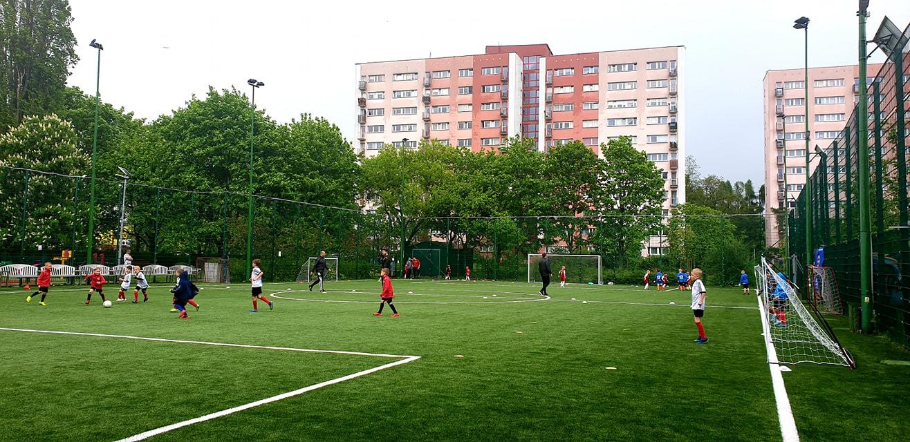 Grupa młodych zawodników biegających po zielonym, ogrodzonym boisku. W tle blok mieszkalny w kolorach różu.