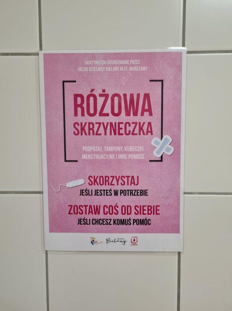 Na pierwszym tle widać różowy plakat z informacjami na temat akcji oraz objaśnieniami dotyczącymi akcji różowych skrzyneczek.