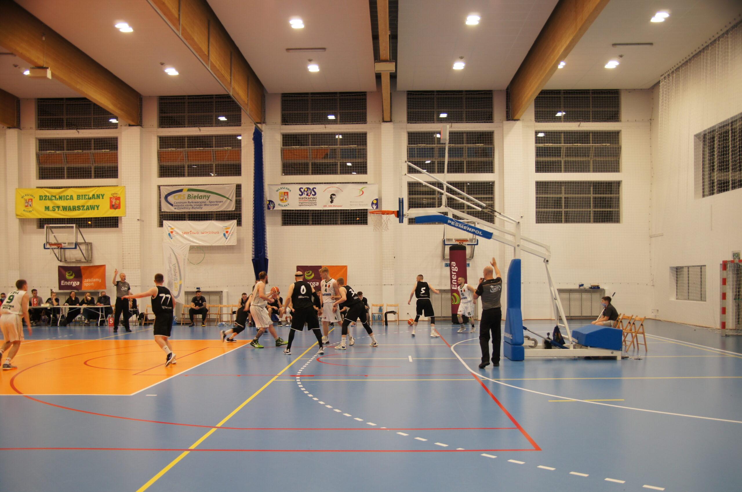 Grupa dorosłych mężczyzn grających w koszykówkę podczas turnieju na terenie Hali Sportowej CRS Bielany. Z tyłu widoczne banery, w tym jeden z logiem CRS Bielany.