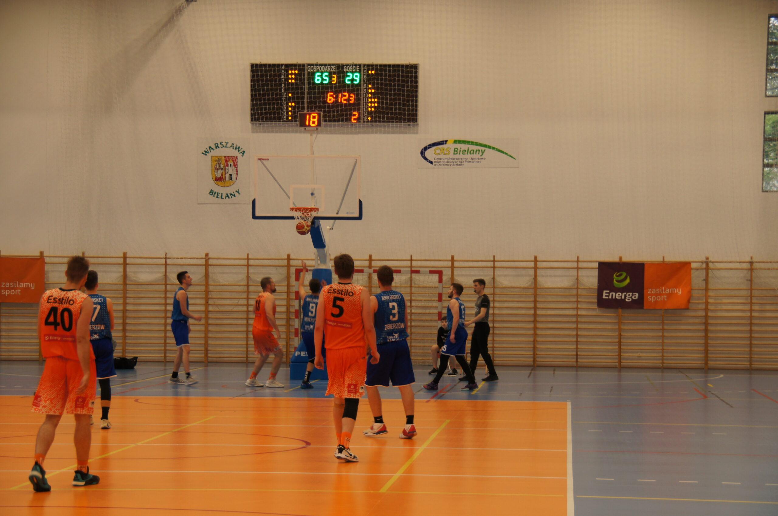 upa dorosłych mężczyzn grających w koszykówkę podczas turnieju na terenie Hali Sportowej CRS Bielany. Z tyłu widoczni również sędziowie oraz banery, w tym jeden z logiem CRS Bielany.