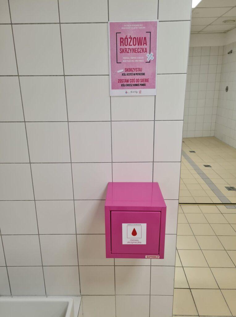 Na pierwszym tle widać zamkniętą różową skrzyneczkę ze środkami higieny takimi jak podpaski, tampony. Skrzyneczka jest zamontowana w jasnej, białej łazience CRS Bielany. Nad nią wisi różowy plakat z informacjami na temat akcji oraz objaśnieniami.