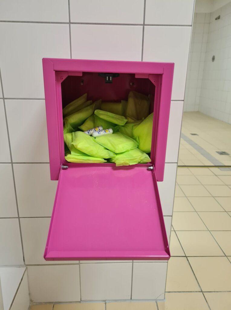 Na pierwszym tle widać otwartą różową skrzyneczkę ze środkami higieny takimi jak podpaski, tampony. Skrzyneczka jest zamontowana w jasnej, białej łazience CRS Bielany.