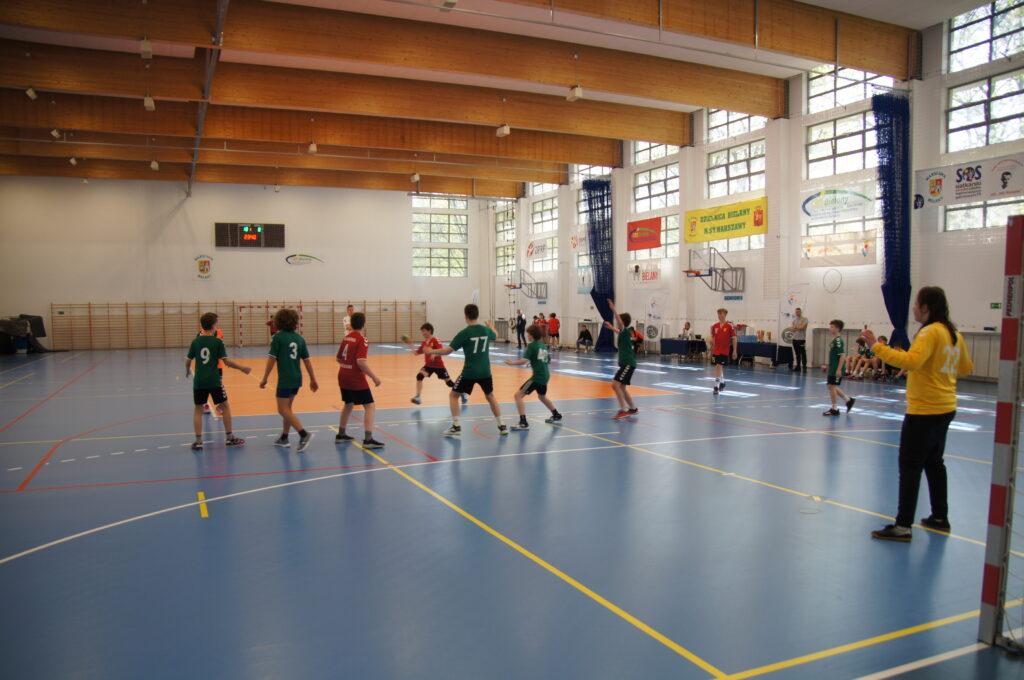 Młodzi zawodnicy biegający po boisku hali sportowej CRS Bielany.  Na drugim planie znajdują się trenerzy oraz sędziowie turnieju.