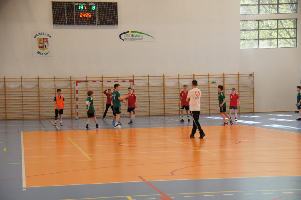 Młodzi zawodnicy biegający po boisku hali sportowej CRS Bielany wraz trenerem.   Na drugim planie znajdują się loga Dzielnicy Bielany oraz CRS Bielany.
