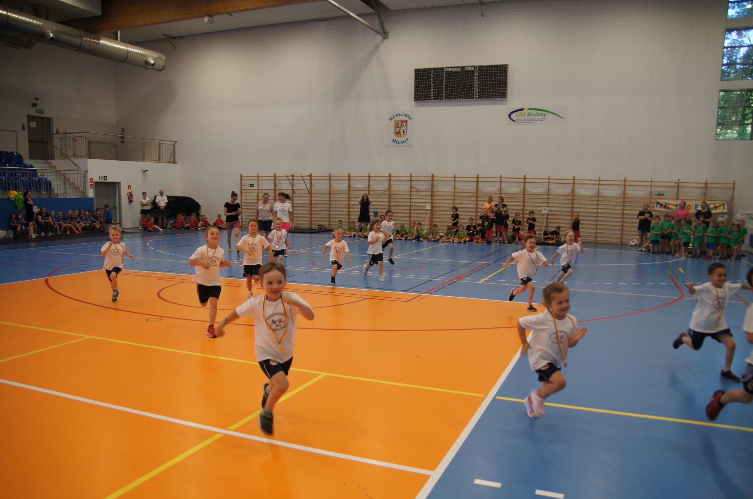 Małe dzieci biegną podczas zawodów sportowych.