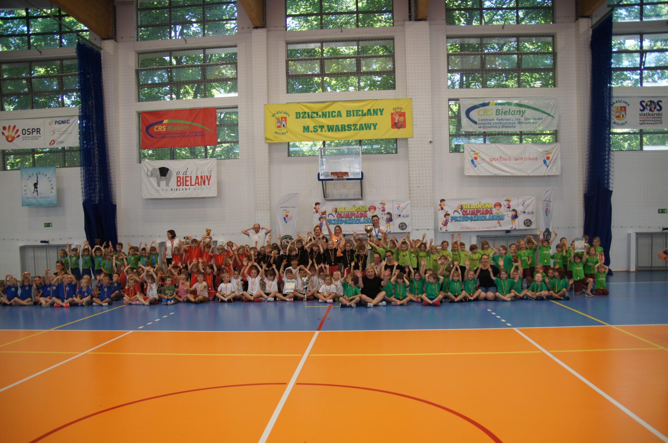 Duża ilość dzieci na zbiorowym zdjęciu wraz z nauczycielami i trenerami.