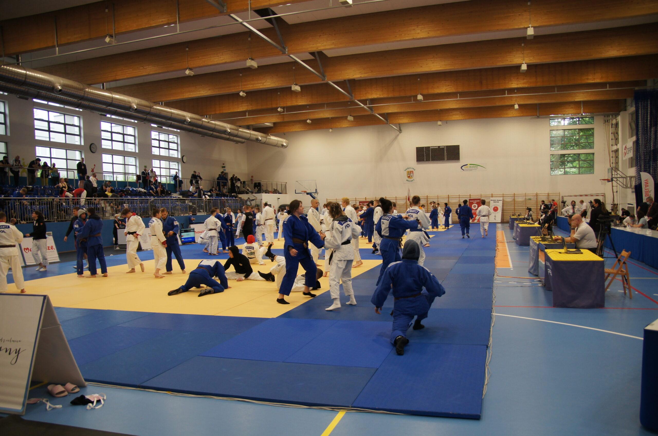 Hala sportowa podczas zawodów Judo. Na środku sali zawodnicy w białych oraz granatowych strojach. Po prawej stronie sędziowie oraz przybyli goście, po prawej publiczność.