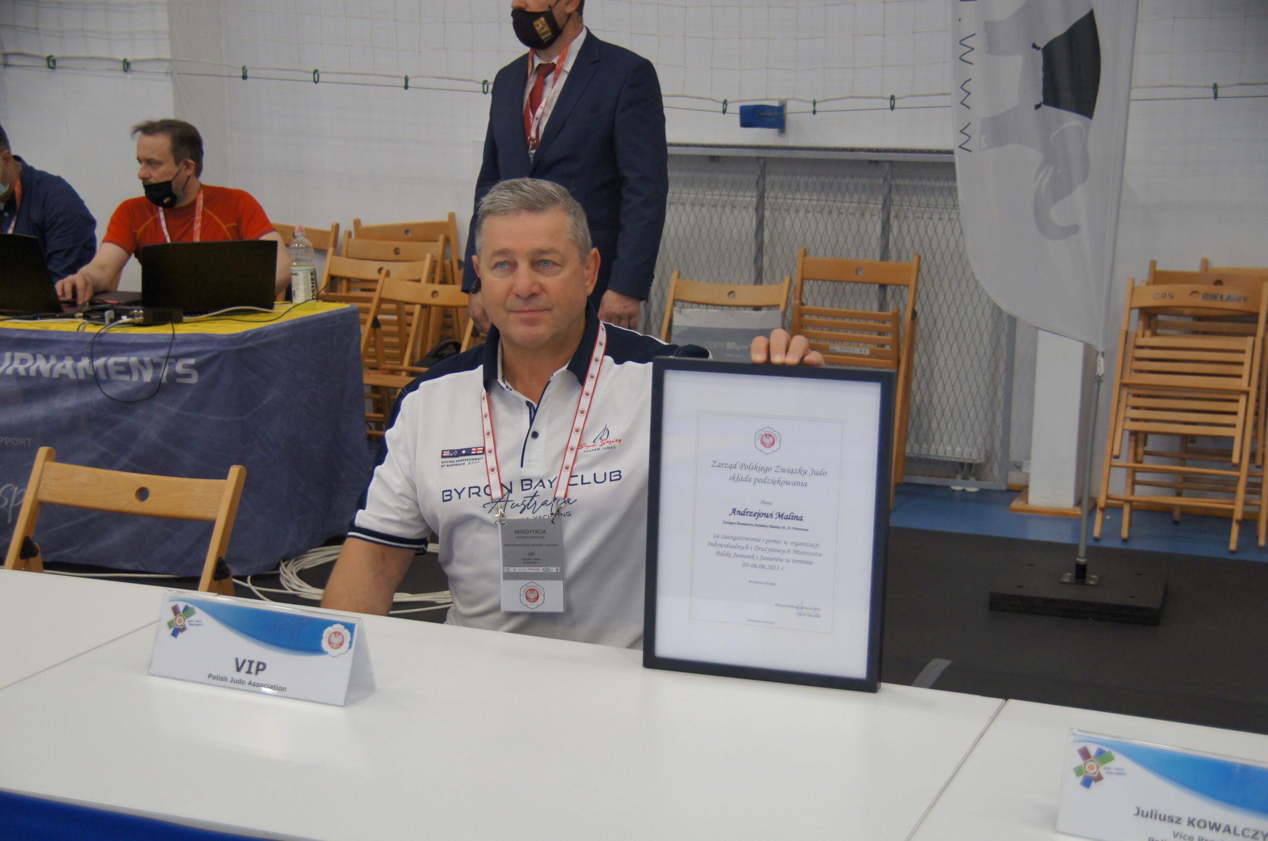 Kilka osób dorosłych za stołami sędziowskimi, w tym Zastępca Burmistrza Dzielnicy Andrzej Malina pokazujący dyplom.