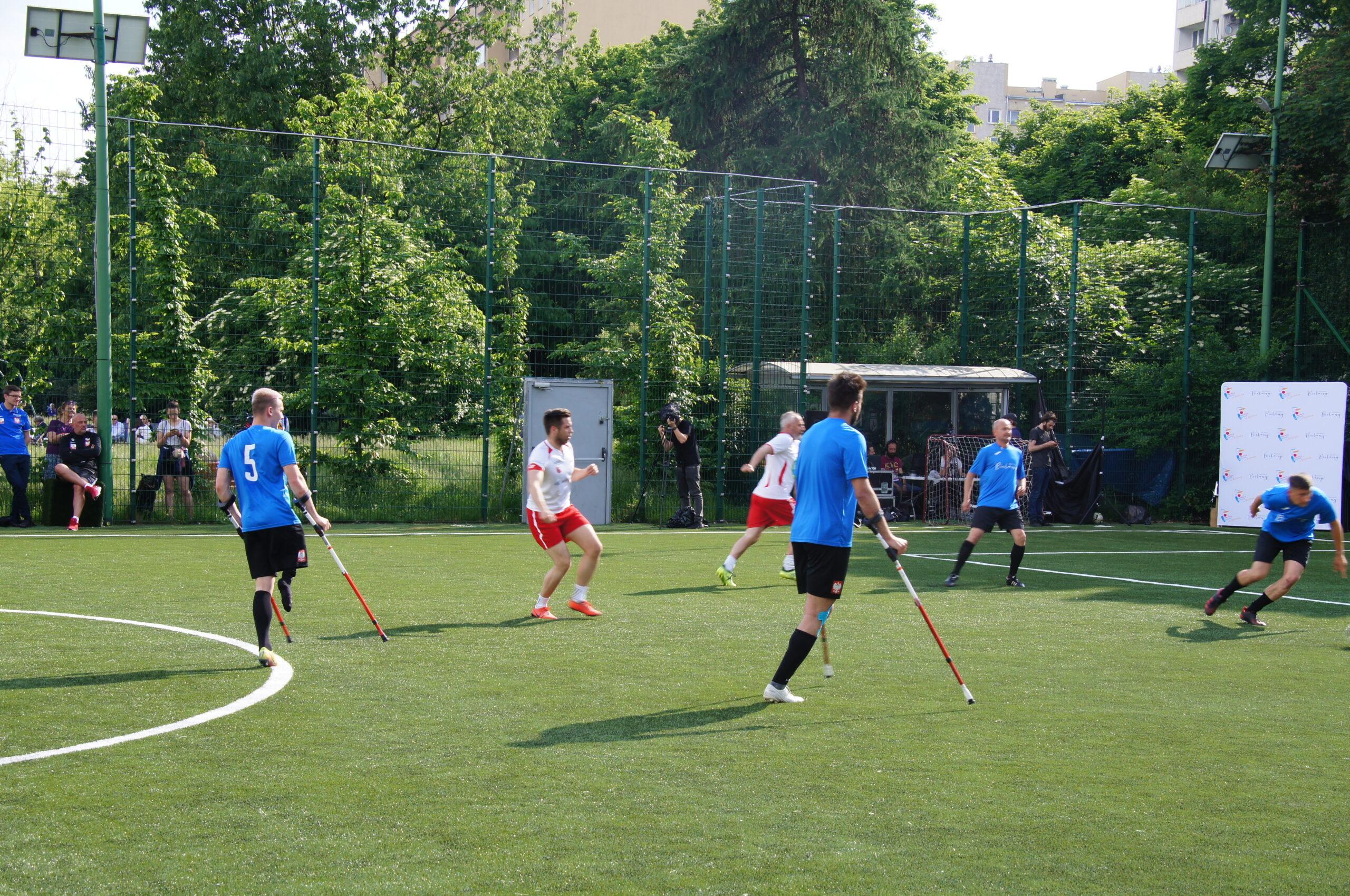 Na zielonej murawie boiska mężczyźni grają w piłkę nożną. Dwóch z nich to zawodnicy niepełnosprawni, podpierający się na kulach. W tle zielone drzewa oraz osoby obserwujące zawodników.