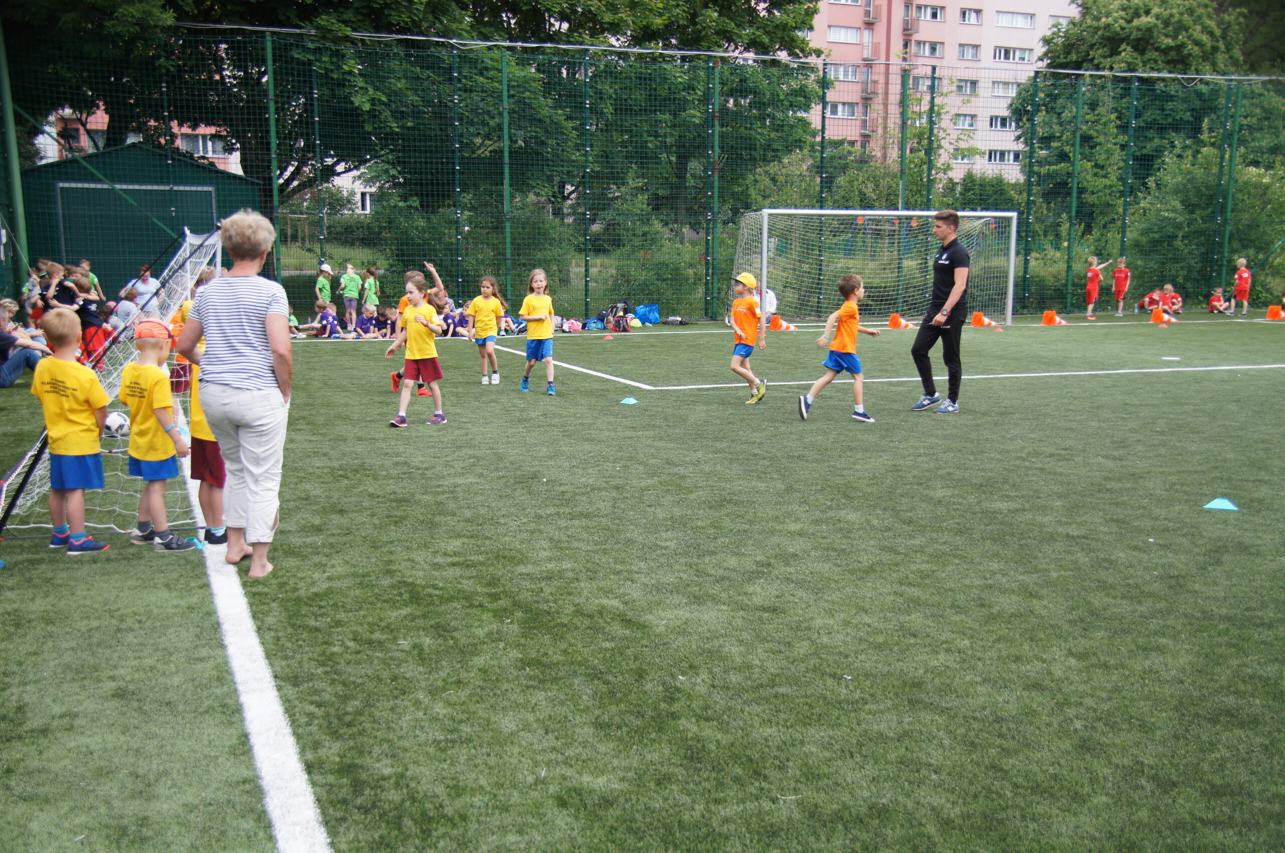Młodzi zawodnicy, przedszkolaki grają na zielonej murawie boiska zewnętrznego Syrenka.