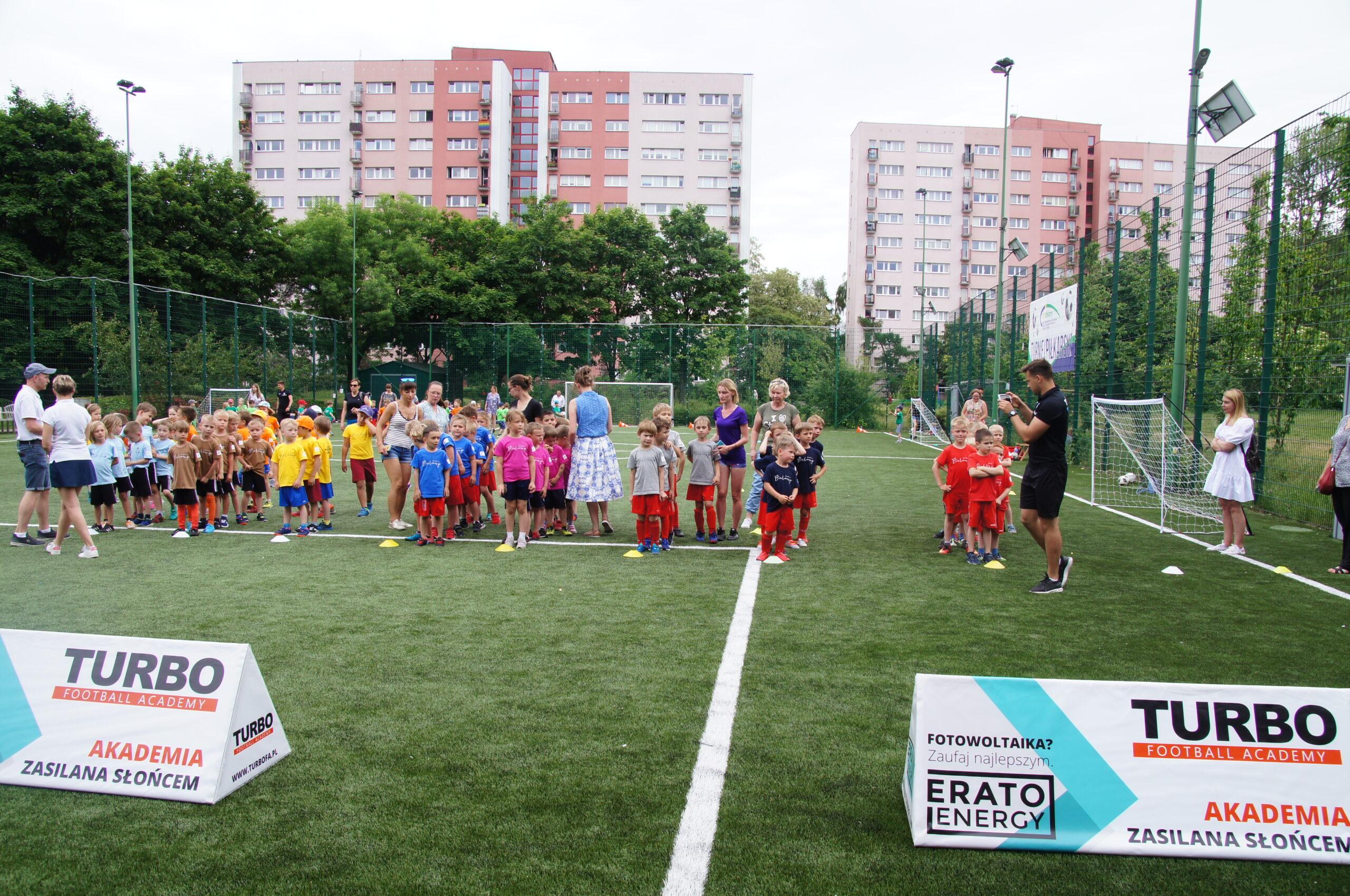 Młodzi zawodnicy, przedszkolaki pozują na zielonej murawie boiska zewnętrznego Syrenka.