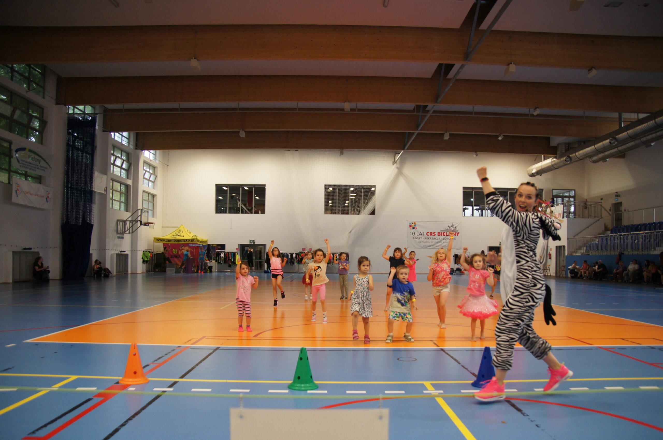 dzieci z instruktorką tańczą na hali sportowej.