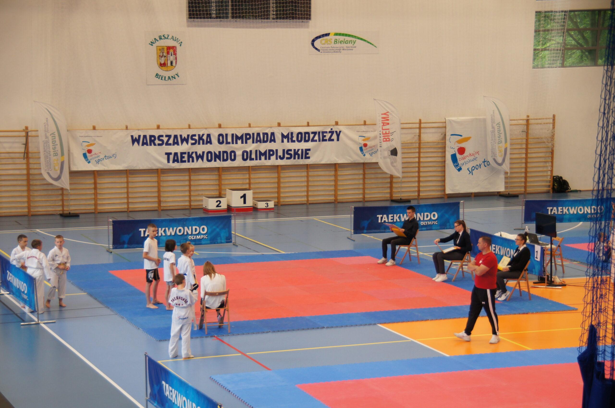 Duża ilość dzieci przygotowujące się do zawodów na hali sportowej.