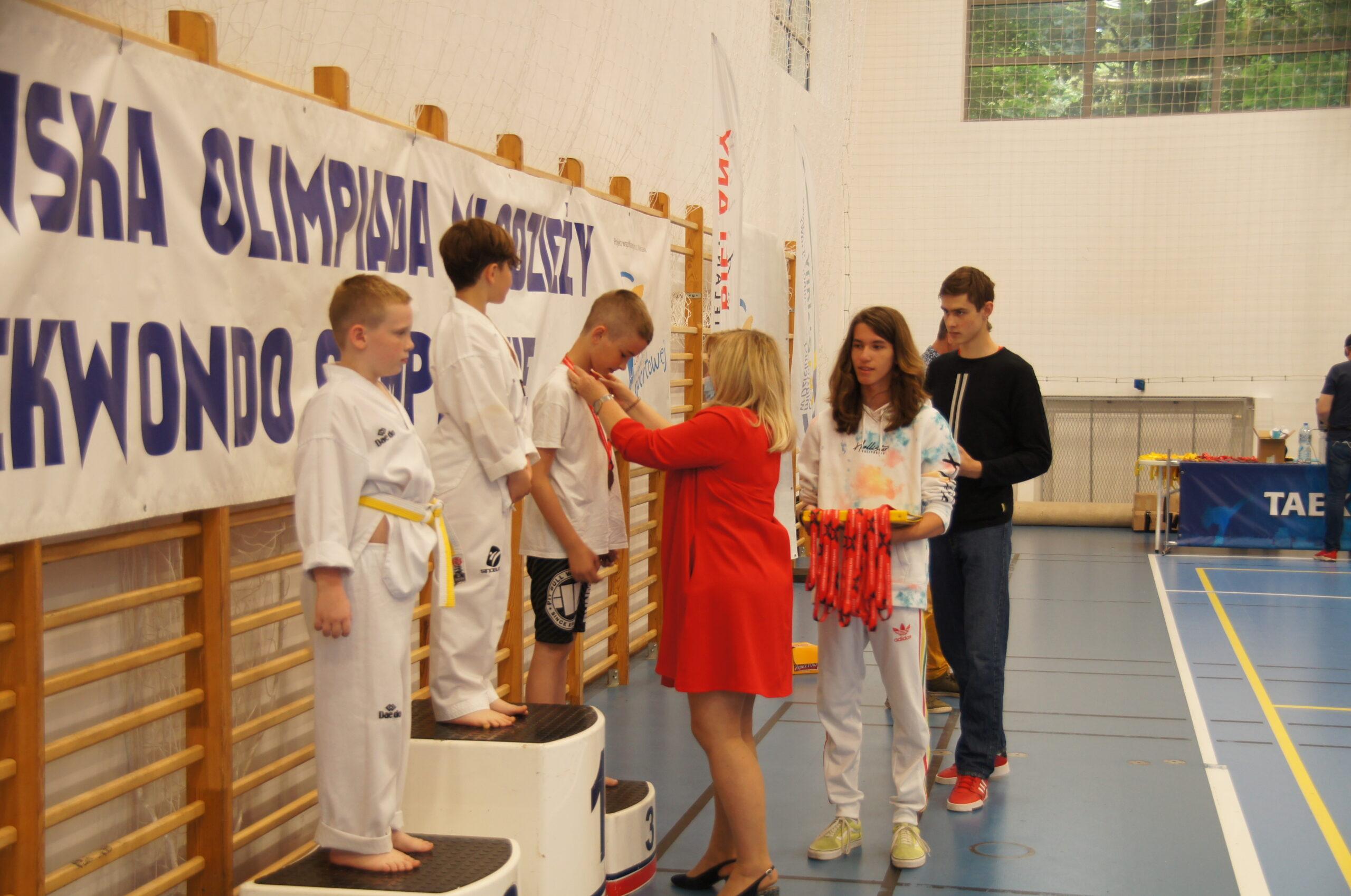 Dekoracja młodych zawodników na hali sportowej.