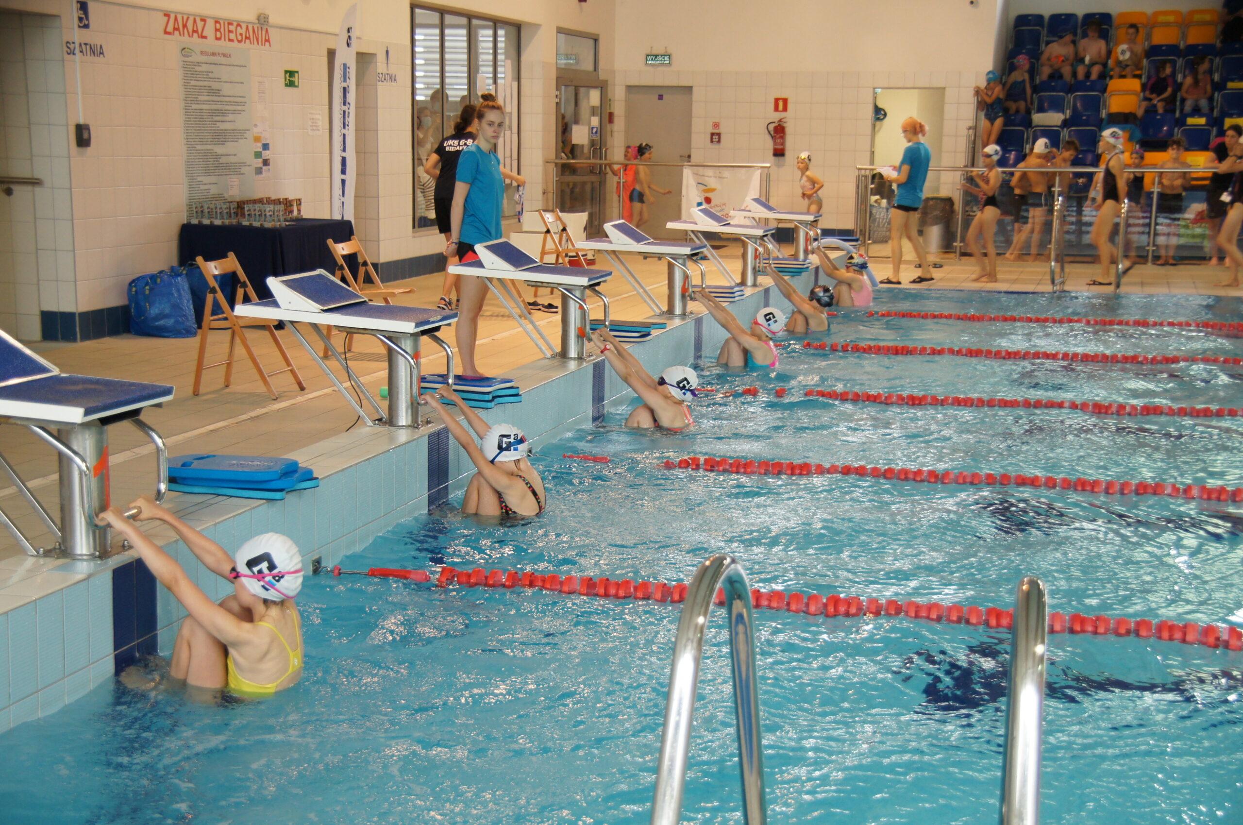 Dzieci w pozycji do rozpoczęcia zawodów w pływaniu.