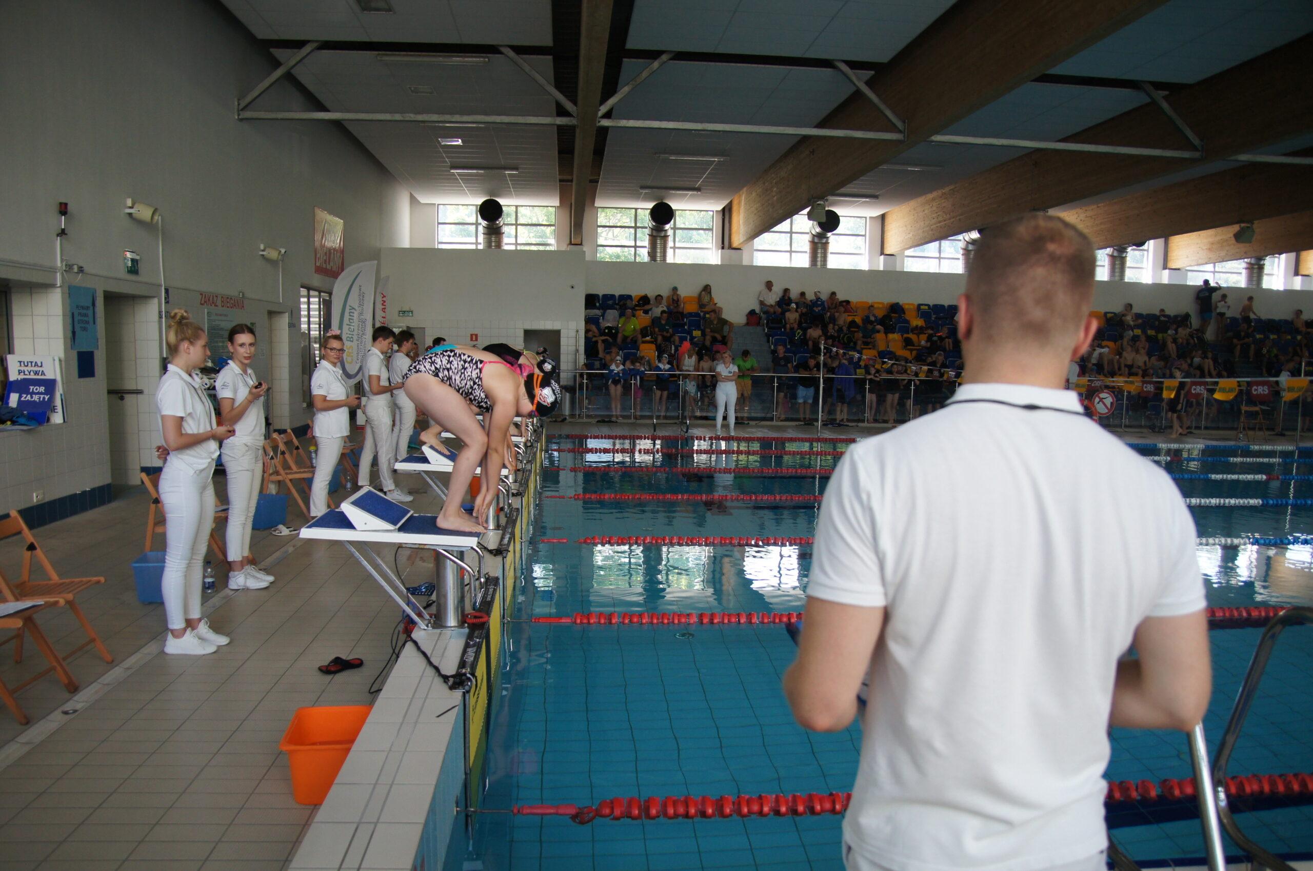 Pływalnia CRS Bielany, widać startujących zawodników i trenerów.