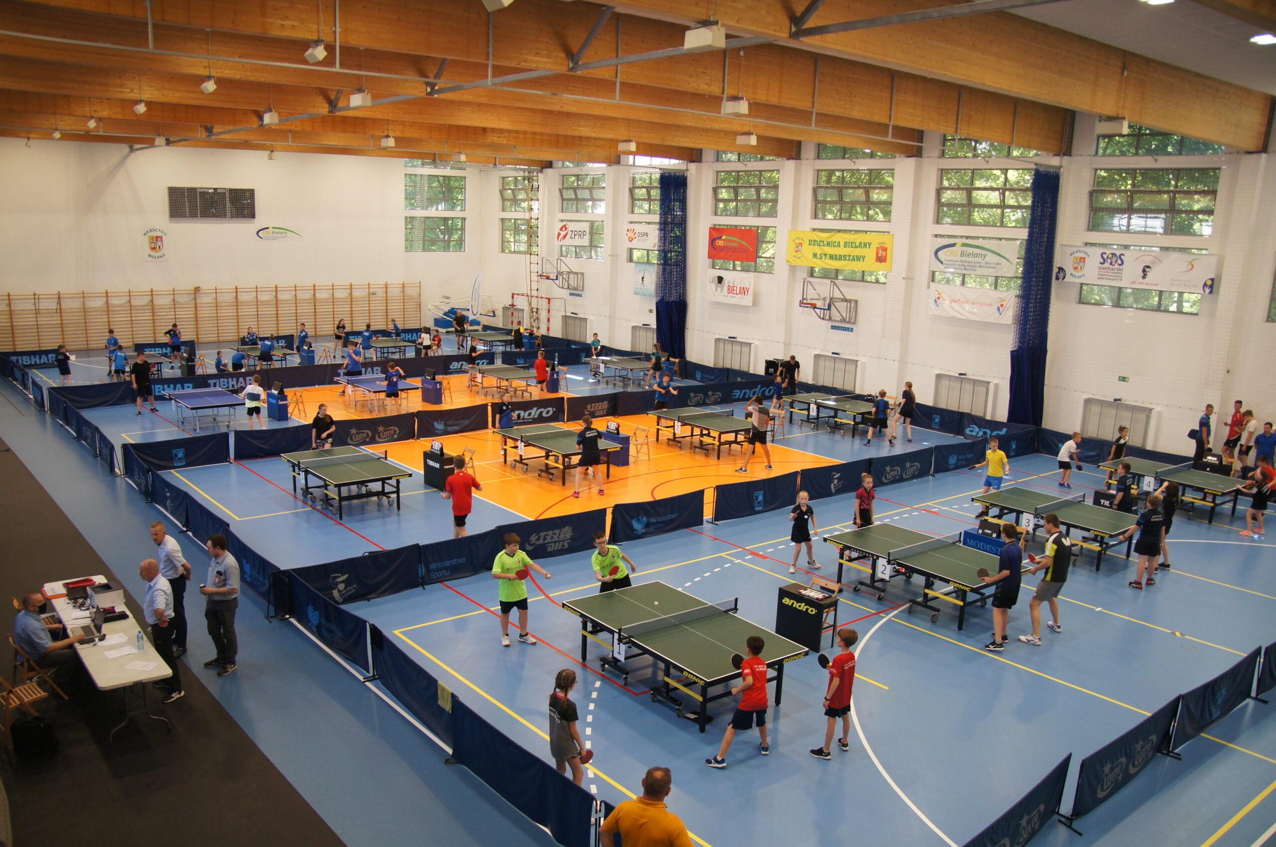Zawodnicy grający w tenisa stołowego w hali sportowej.