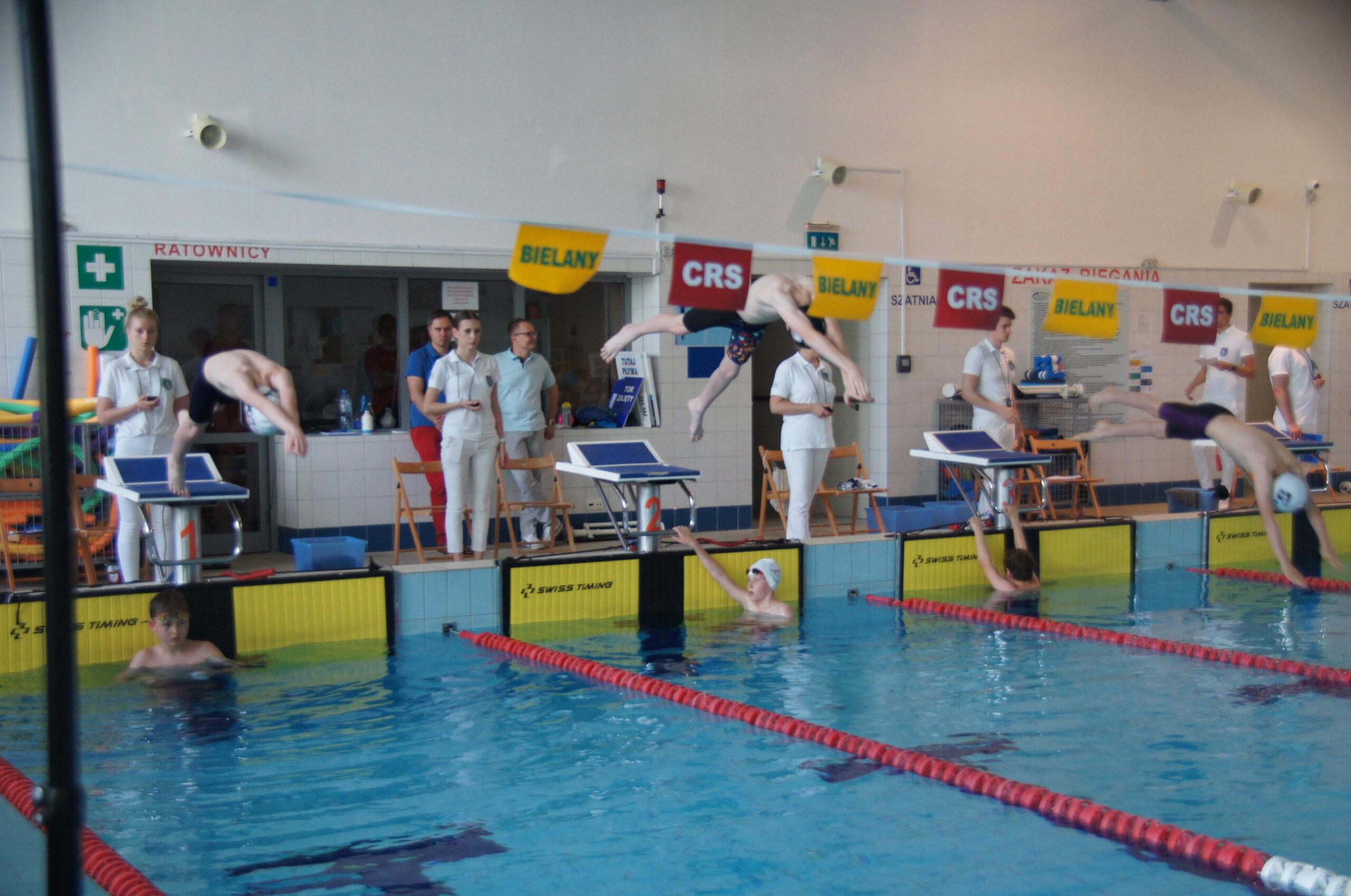Pływalnia CRS Bielany, widać startujących zawodników, trenerów oraz burmistrzów dzielnicy