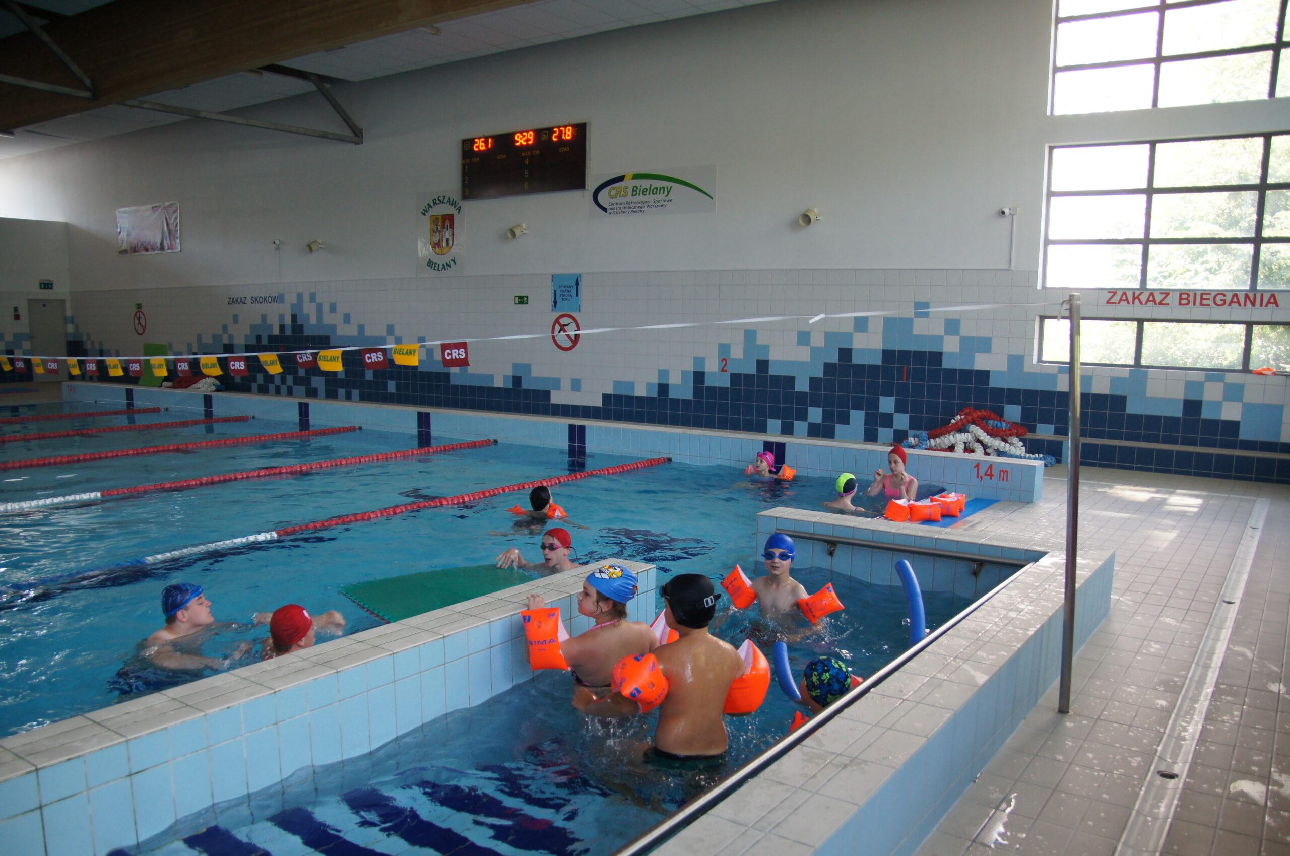 Grupa pływających dzieci na pływalni.