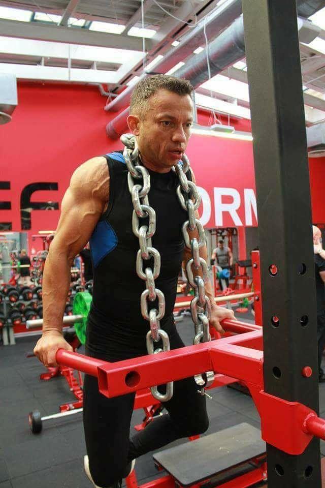 dorosły człowiek, trener ćwiczy na siłowni na profesjonalnym sprzęcie.