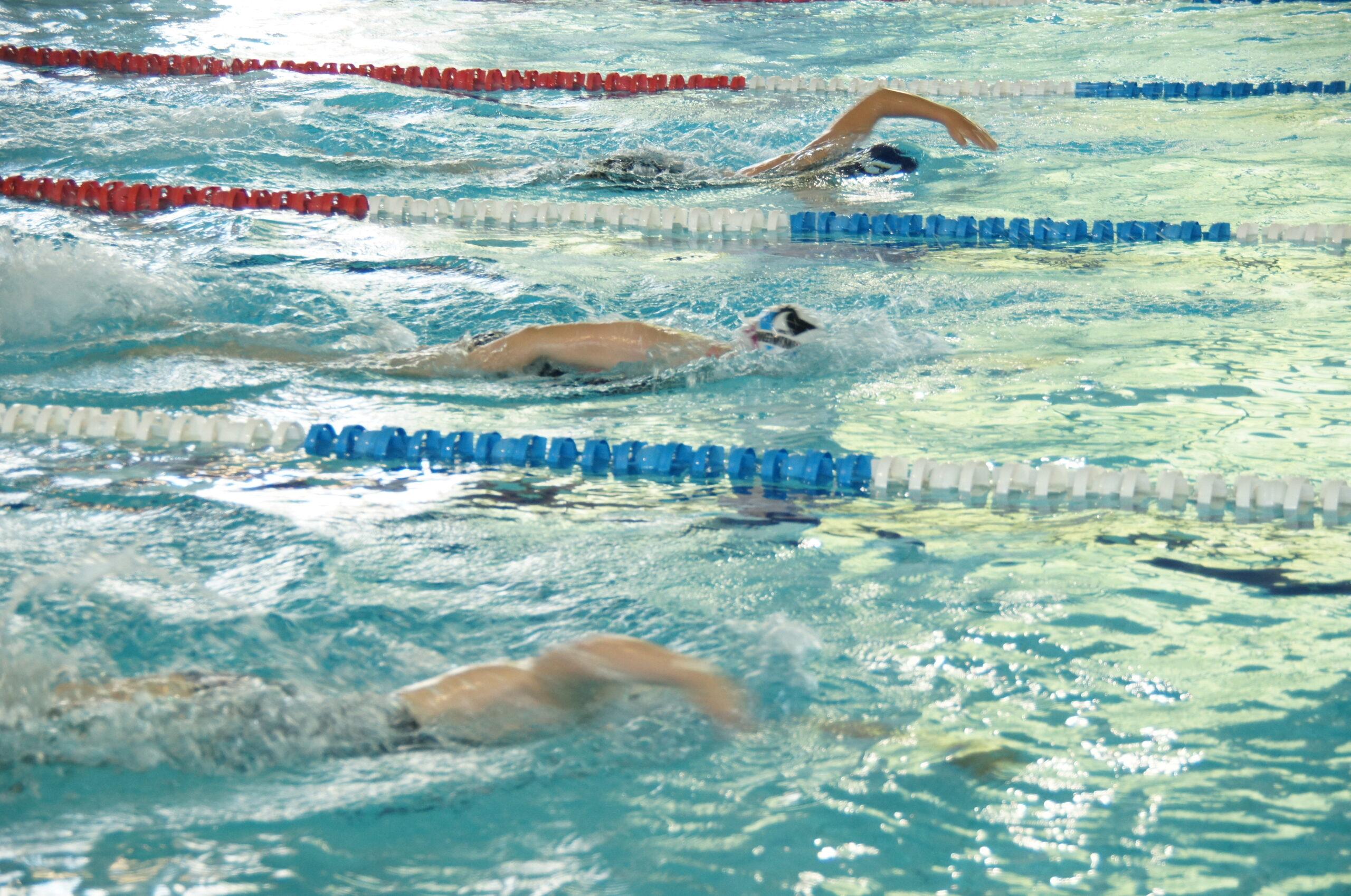 pływanie: Młodzi zawodnicy płyną w wodzie na pływalni.