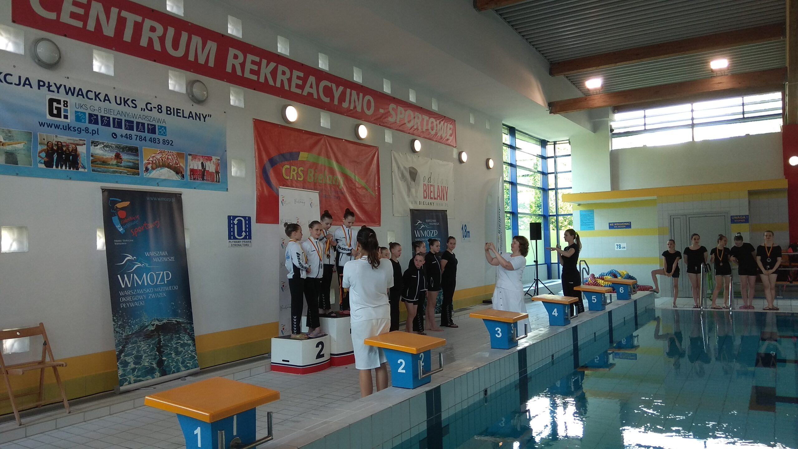 Wręczanie nagród po zawodach pływackich, pozowanie do zdjęć.