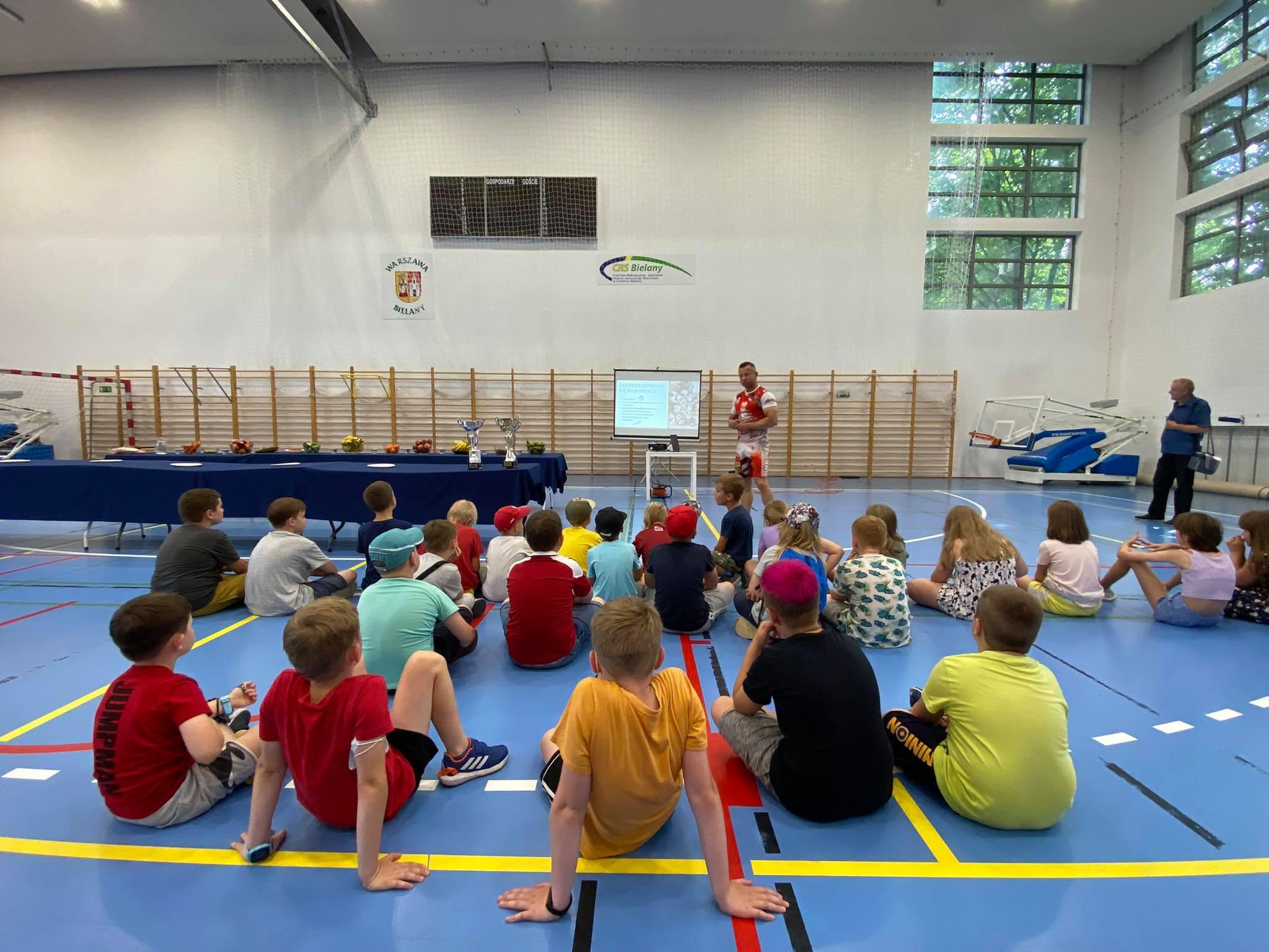 Grupa dzieci słuchających pogadanki na hali sportowej.