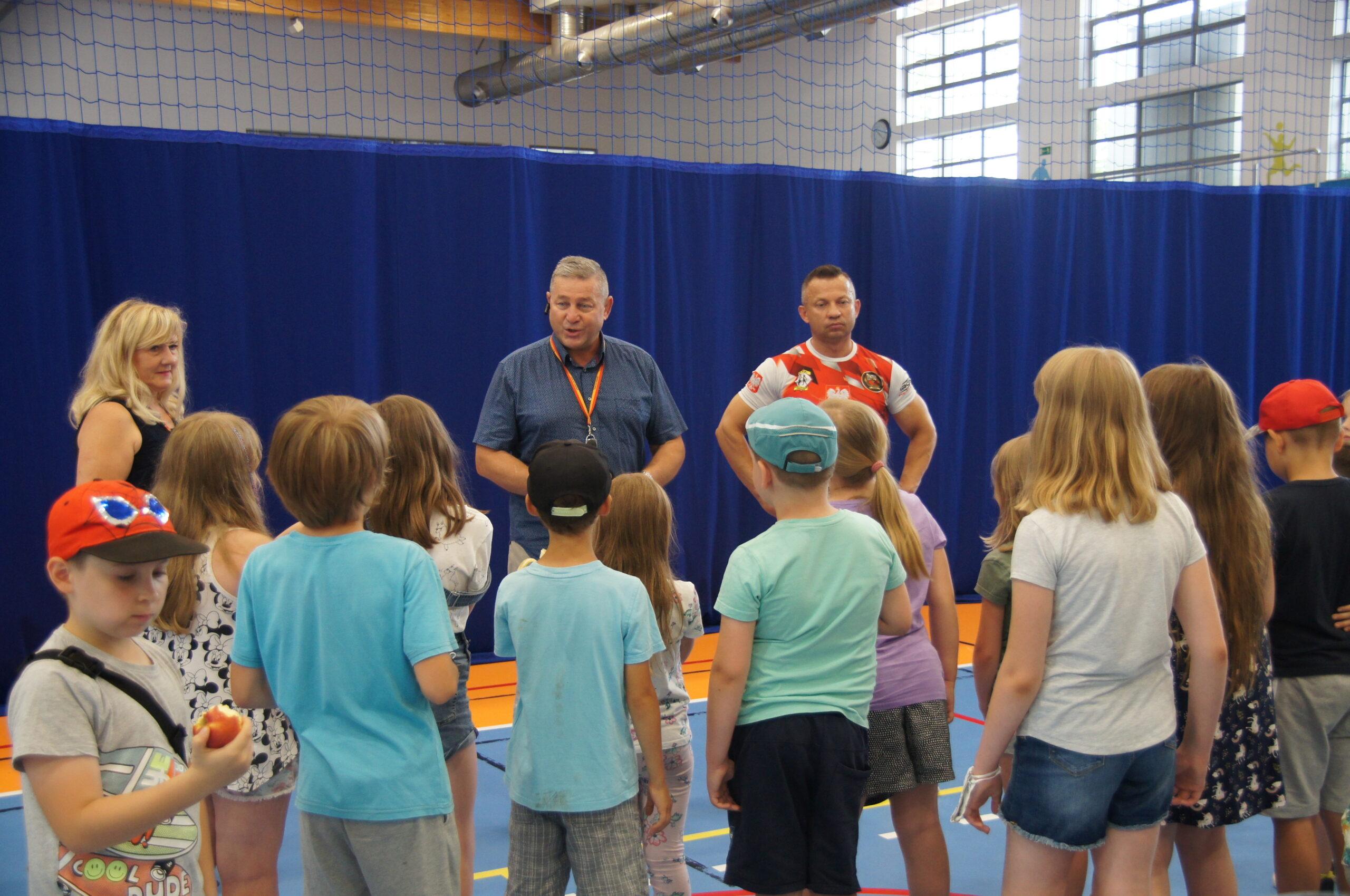 Grupa dzieci słuchająca pogadanki oraz 3 osoby dorosłe.