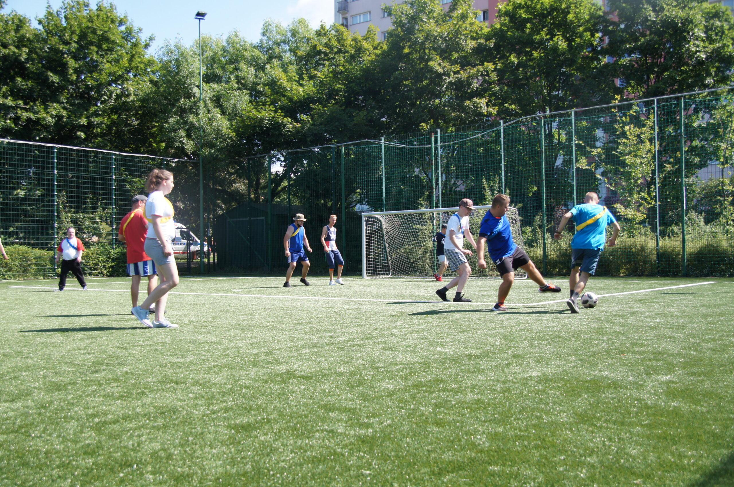 Grupa zawodników grająca w piłkę nożnej na zielonej murawie.