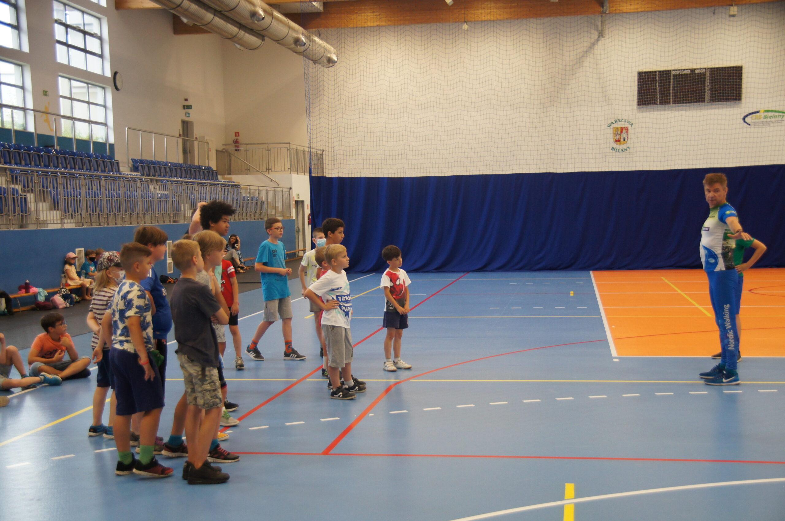 Grupa dzieci trenująca i bawiąca się na hali sportowej wraz z trenerem.