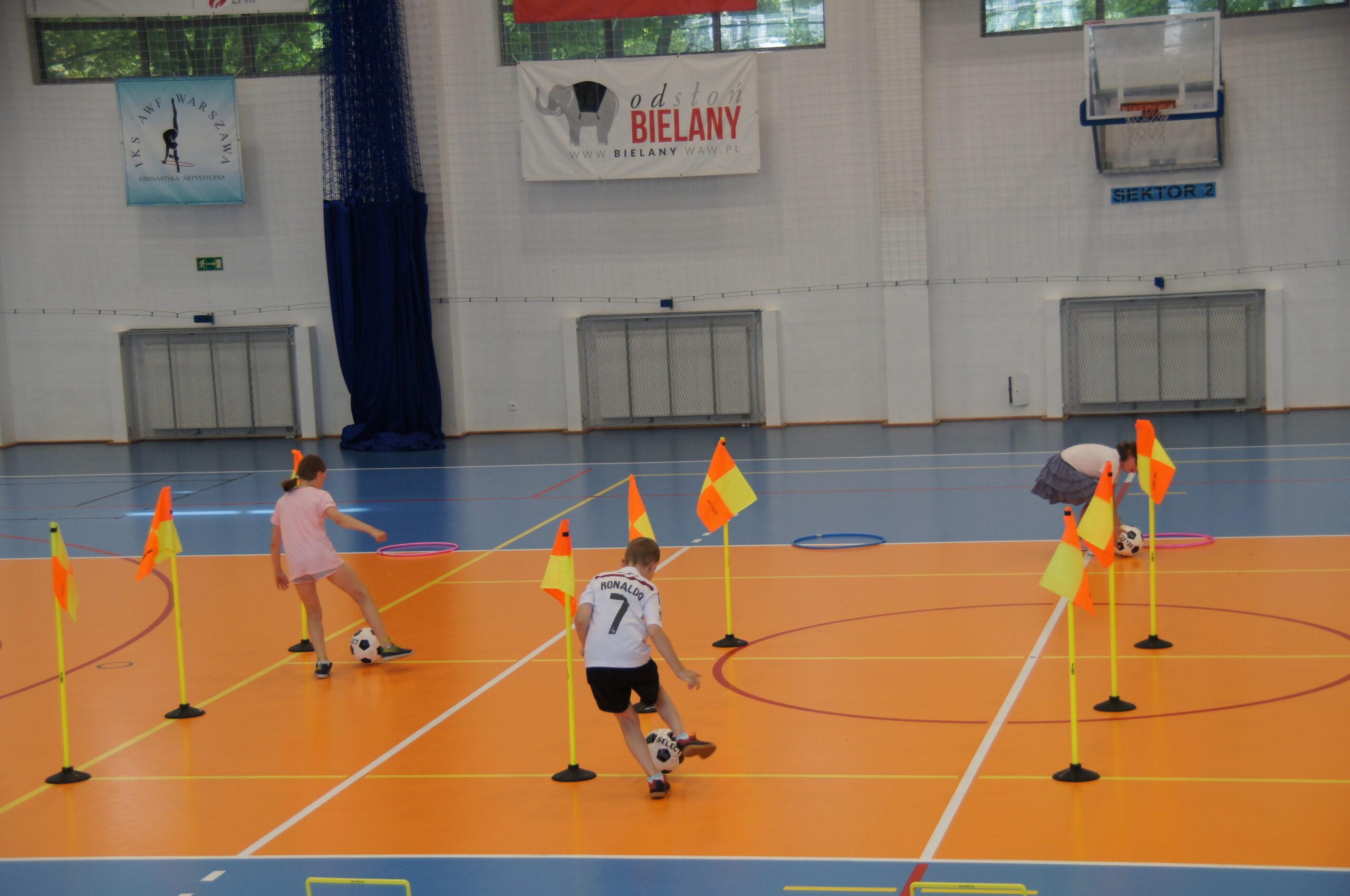 Trójka dzieci bawiących się na hali CRS Bielany.