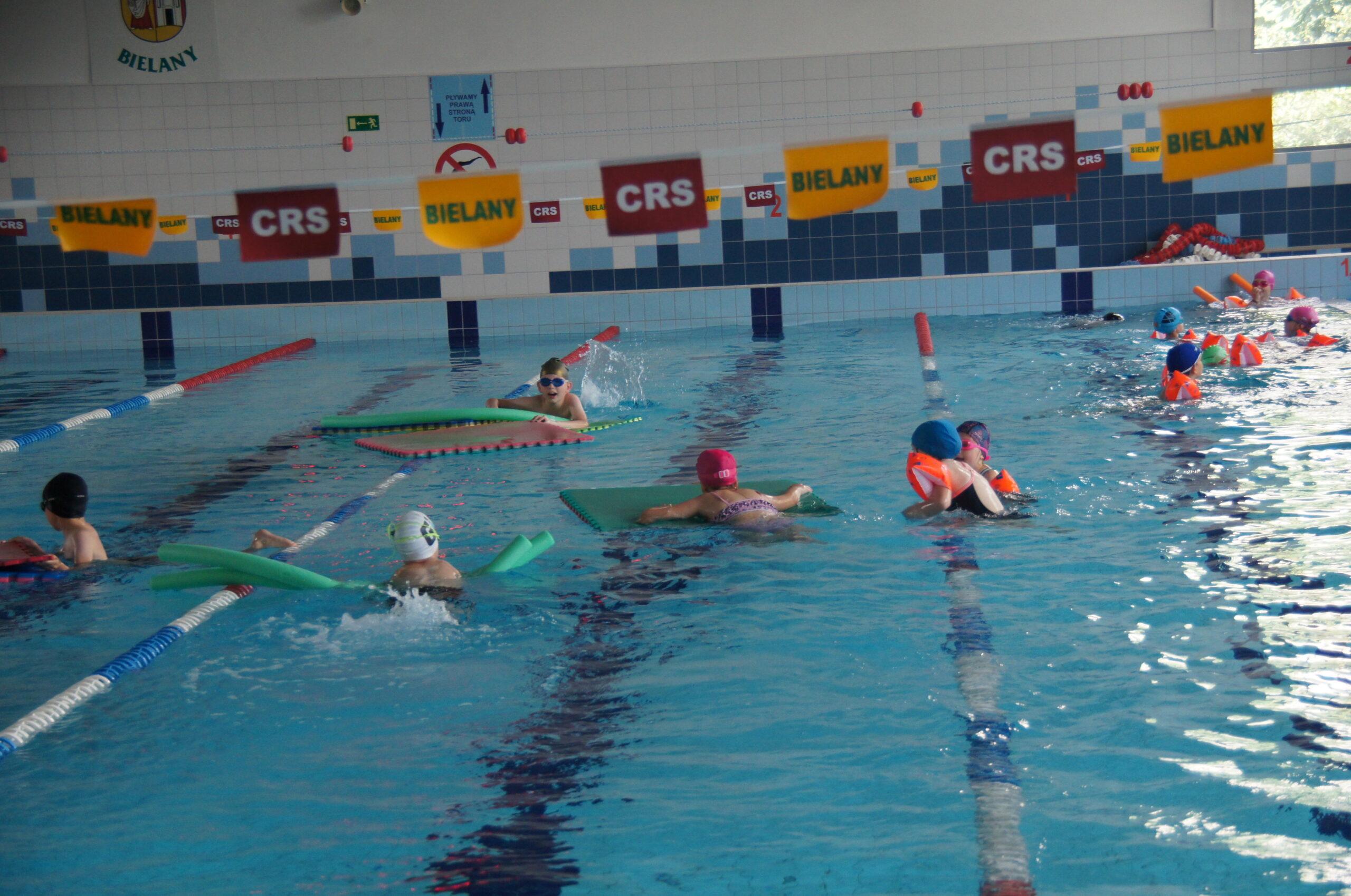 Grupa dzieci pływająca na pływalni CRS Bielany.