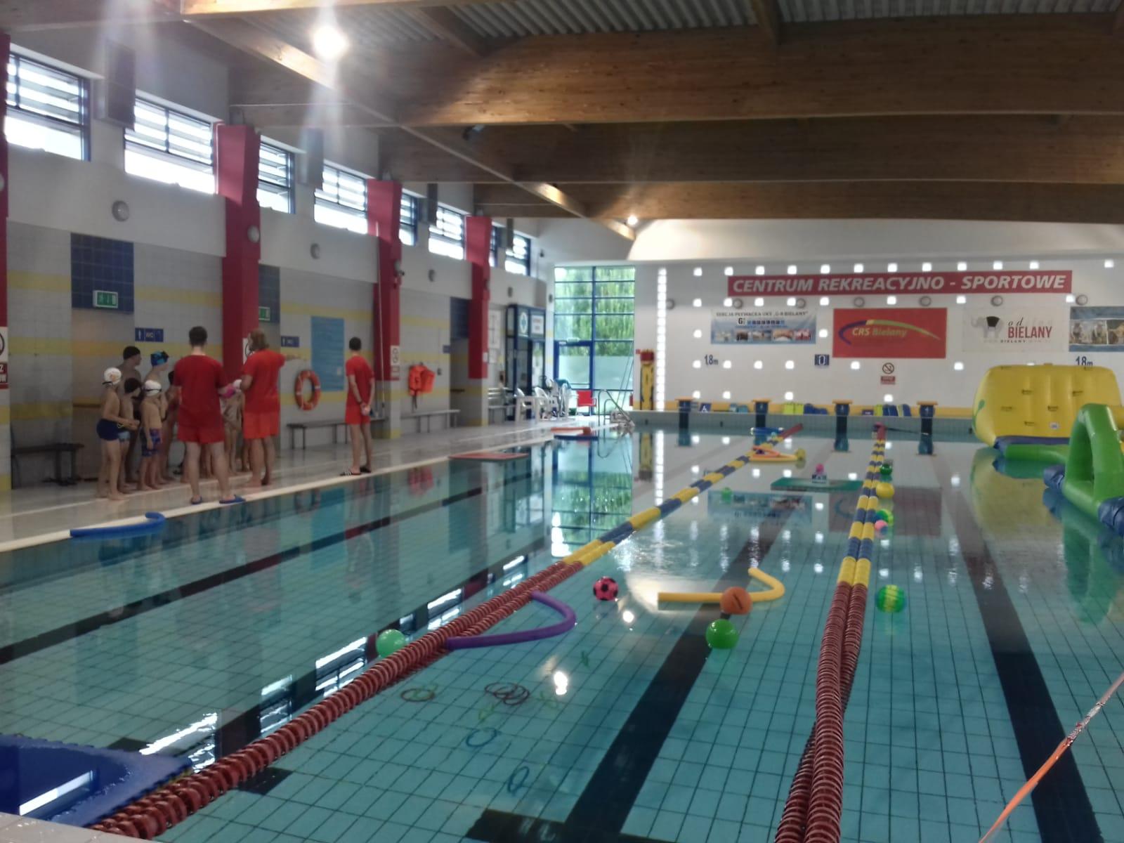 Grupa dzieci na pływalni słucha pogadanki na temat bezpieczeństwa.