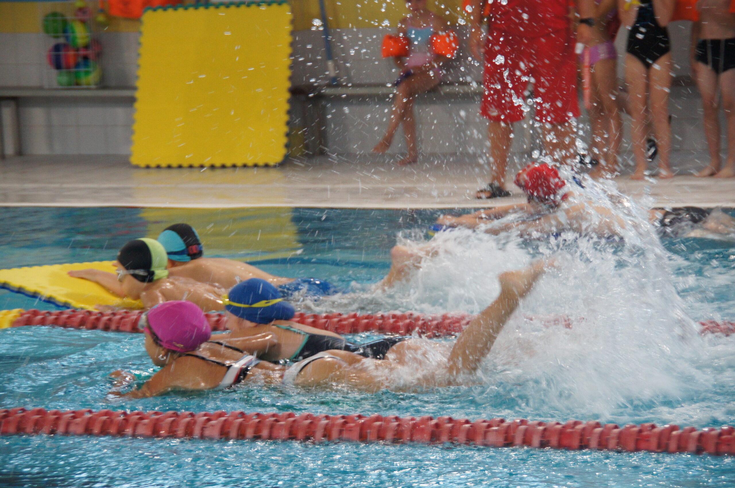 Grupa dzieci pływająca w basenie.