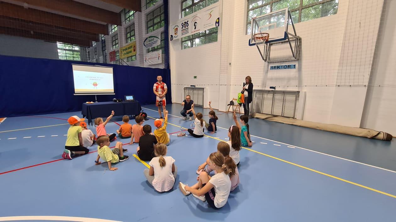 Grupa dzieci oraz trzy osoby dorosłe podczas wykładu na hali sportowej oraz wyświetlana prezentacja.