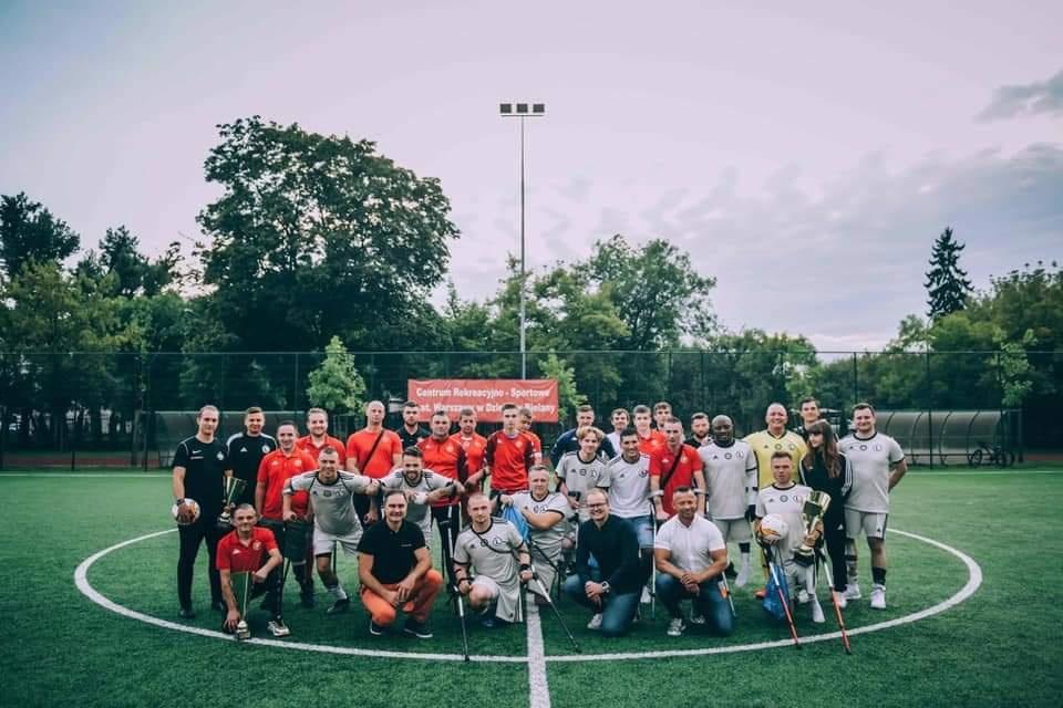 Duża grupa dorosłych zawodników AMP Futboll wraz z przybyłymi gośćmi pozuje do zdjęcia