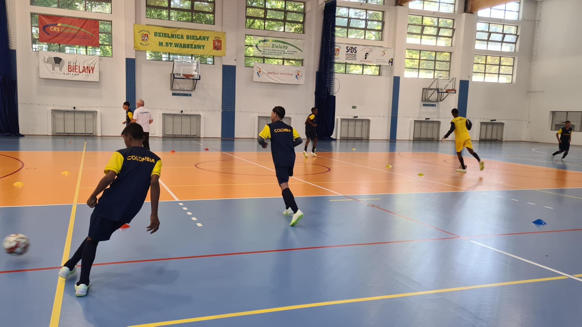 Młodzi chłopcy z Kolumbii grający w piłkę nożną na hali sportowej.